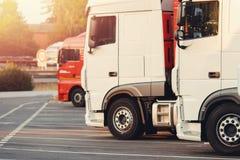Tauschend auf LKWs, werden weiße Autos im Parkplatz geparkt, bereit, Logistikweg anzustellen lizenzfreie stockfotografie