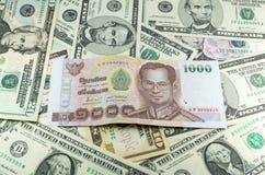 Tausend thailändischer Baht (THB) auf Hintergrund vieler Dollar Stockfotos