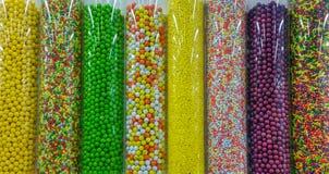 Tausenden der bunten Süßigkeiten in den Kunststoffrohren stockbilder