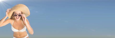 Tausendjährige Frau im Bikini, im Hut und in der Sonnenbrille gegen Sommerhimmel mit Aufflackern Lizenzfreie Stockfotografie