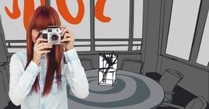 Tausendjährige Frau mit Kamera gegen orange und graue Hand gezeichnetes Büro Stockbilder