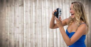 Tausendjährige Frau mit Kamera gegen undeutliche Täfelung Lizenzfreie Stockfotos