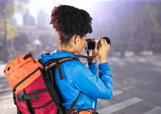 Tausendjähriger Wanderer mit Kamera gegen undeutliche Straße mit Aufflackern Stockfoto