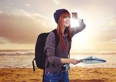 Tausendjähriger Wanderer mit Karte auf Sonnenuntergangstrand mit Aufflackern Stockbilder