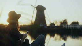 Tausendjähriges Mädchen sitzt mit Telefon auf Seepier Einstellung Sun Frau, die draußen Einkaufsapp verwendet Alte niederländisch stock video