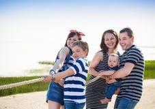 Tauziehen - Familie, die auf dem Strand spielt Stockfotos