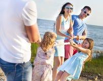 Tauziehen - Familie, die auf dem Strand spielt Klappstuhl auf Strand in Brighton Stockfotografie