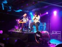 Tavana et Keith Batlin jouent la guitare et l'harmonica sur l'étape Photographie stock libre de droits