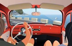 tavelling在减速火箭的汽车的海岸路的年轻夫妇 免版税库存照片