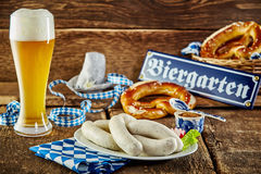 Tavern meal for the Munich Oktoberfest. With traditional veal sausages and pretzels served with an ice cold frothy beer in a long glass on a rustic counter stock photo