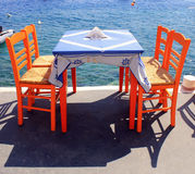 Tavern with orange wooden chairs by the sea coast, Santorini Royalty Free Stock Photos