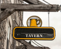 Tavern Sign. Hanging black wooden sign advertising for a tavern Royalty Free Stock Image
