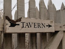 TAVERN. Weathered wooden sign at the back gate for a tavern in Williamsburg, Virginia; black paint on white wood stock photography