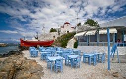Taverna da praia de Mykonos e a igreja Imagem de Stock Royalty Free