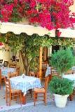 Taverna griego hermoso con las flores de la buganvilla Fotos de archivo libres de regalías