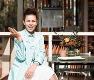 Tavola all'aperto di seduta del caffè di estate della bella dei pantaloni a vita bassa ragazza castana di stile Fotografia Stock