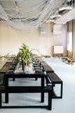 Tavola alla moda, sottotetto Stanza di progettazione nello stile del sottotetto Tavola nera, sedie, piatti, candele Barattoli con Fotografie Stock