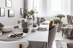 tavola Ben-posta con i piatti ed i vetri in un interno grigio della sala da pranzo Foto reale immagini stock