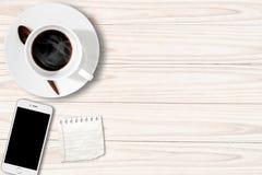 Tavola bianca con la carta per appunti e Smartphone della tazza di caffè Fotografia Stock