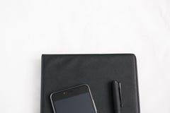 Tavola bianca della scrivania con il computer portatile, lo smartphone, il taccuino e la penna Fotografia Stock Libera da Diritti