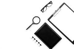 Tavola bianca e nera monocromatica rigorosa della scrivania con il cuscinetto, lente, taccuino, vetri sulla vista superiore del f fotografia stock