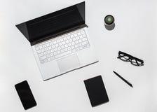 Tavola bianca moderna della scrivania con il computer portatile, lo Smart Phone dello schermo in bianco, gli occhiali alla moda,  Fotografie Stock Libere da Diritti