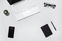 Tavola bianca moderna dello scrittorio del ` s dello studente con il computer portatile, lo Smart Phone dello schermo in bianco,  Fotografie Stock