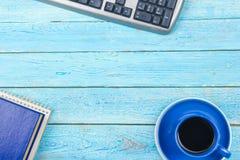 Tavola blu della scrivania con il computer, penna e una tazza di caffè, lotto delle cose Vista superiore con lo spazio della copi Immagine Stock