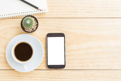 Tavola d'annata della scrivania con lo smartphone, i taccuini, la matita e una tazza di caffè fotografia stock libera da diritti