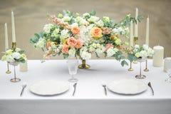 Tavola decorata di nozze per due con la bella composizione del fiore dei fiori, vetri per vino e piatti, all'aperto, fini Fotografia Stock