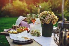 Tavola del giardino di estate decorata con i fiori e le candele, partito di sera con vino immagine stock libera da diritti