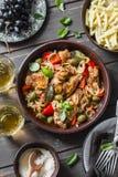 Tavola del pranzo Pollo arrostito con le olive ed i peperoni dolci, pasta, vino bianco su fondo scuro, vista superiore immagine stock libera da diritti