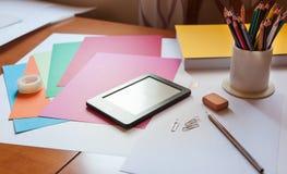 Tavola dell'area di lavoro con gli oggetti ed il libro elettronico dell'ufficio Fotografie Stock
