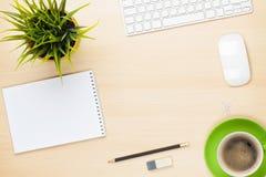 Tavola dell'ufficio con il blocco note, il computer, la tazza di caffè ed il fiore Immagini Stock Libere da Diritti