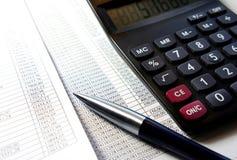 Tavola dell'ufficio con il calcolatore, la penna ed il documento contabile Immagine Stock