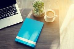 Tavola dell'ufficio con il libro blu della copertura dello schermo in bianco, caffè fresco e fotografie stock