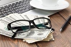 Tavola dell'ufficio con il pc, la tazza di caffè ed i vetri sopra i contanti dei soldi Fotografia Stock