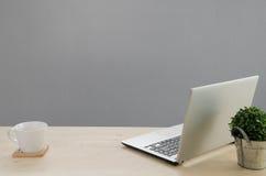 Tavola dell'ufficio con il taccuino, albero verde sul canestro e coffe bianco fotografia stock