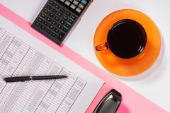 Tavola dell'ufficio con la penna, il calcolatore e la tazza di coffe colore fotografia stock libera da diritti