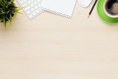 Tavola dell'ufficio con la tazza del blocco note, del computer e di caffè Fotografia Stock