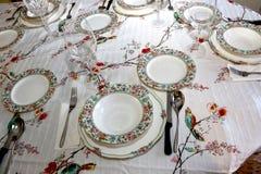 Tavola della sala da pranzo con i piatti ed i vetri fotografia stock