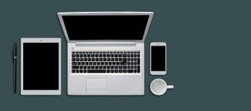 Tavola della scrivania con gli aggeggi, la tazza e la penna moderni Dispositivi moderni su superficie piana: compressa, smartphon Fotografia Stock