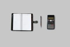 Tavola della scrivania con i rifornimenti, il taccuino, il calcolatore e la penna T fotografia stock libera da diritti
