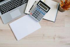 Tavola della scrivania con il computer, i rifornimenti ed il calcolatore Vista superiore con lo spazio della copia Immagini Stock