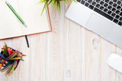 Tavola della scrivania con il computer, i rifornimenti ed il fiore Immagine Stock Libera da Diritti