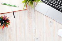 Tavola della scrivania con il computer, i rifornimenti ed il fiore Fotografia Stock