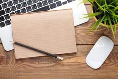 Tavola della scrivania con il computer, i rifornimenti ed il fiore Fotografie Stock Libere da Diritti