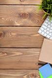 Tavola della scrivania con il computer, i rifornimenti ed il fiore Fotografie Stock