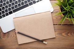 Tavola della scrivania con il computer, i rifornimenti ed il fiore Immagini Stock Libere da Diritti