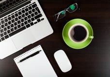 Tavola della scrivania con il computer, i rifornimenti, il caffè ed i vetri Fotografie Stock